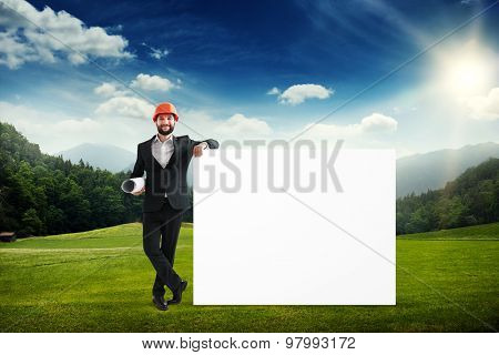 smiley businessman in formal wear and orange helmet holding big empty white banner at outdoor