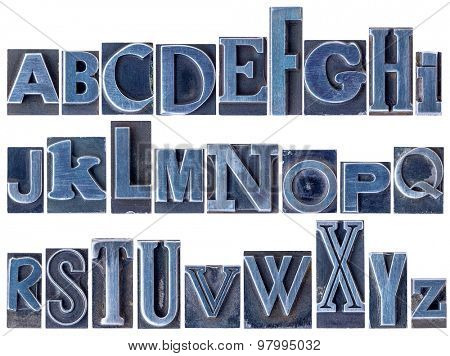English alphabet - a collage of 26 isolated letters in letterpress metal type printing blocks, a variety of mixed fonts stained by blue ink