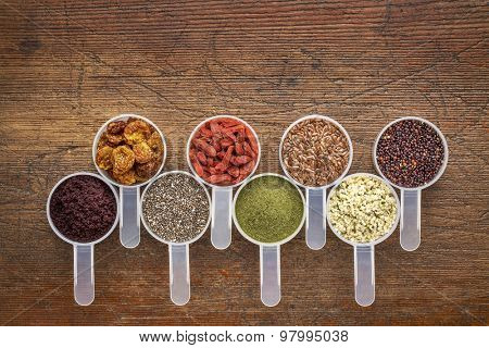 superfood abstract (wheatgrass, acai berry, goji berry, flax seed,chia seed,goldenberry, hemp seed, quinoa grain) - top view of measuring scoop against rustic wood with a copy space