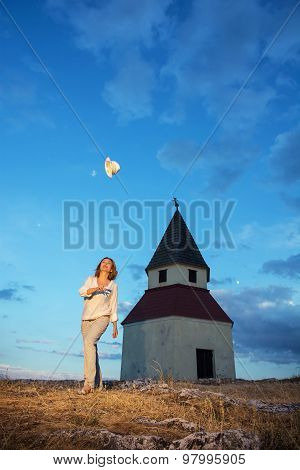 Young Woman Throws Up Her Hat By Sunset Near The Church