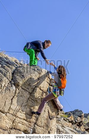 Climber helps her partner to rich the summit Two female climbers, one drags the hand of another. Deep blue sky on the background poster