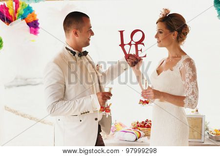 Beautiful  Gorgeous Blonde Bride  And Stylish Groom With Red Letters Love, Hawai  Colorful Sand