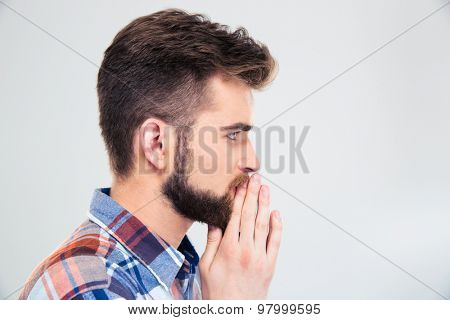 Side view protrait of a casual man praying isolated on a white background