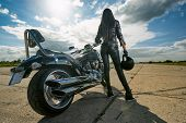 Biker girl in leather jacket standing by a motorcycle. Rear view poster