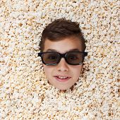 Grinning flaunt young boy in stereo glasses watching a movie from popcorn poster