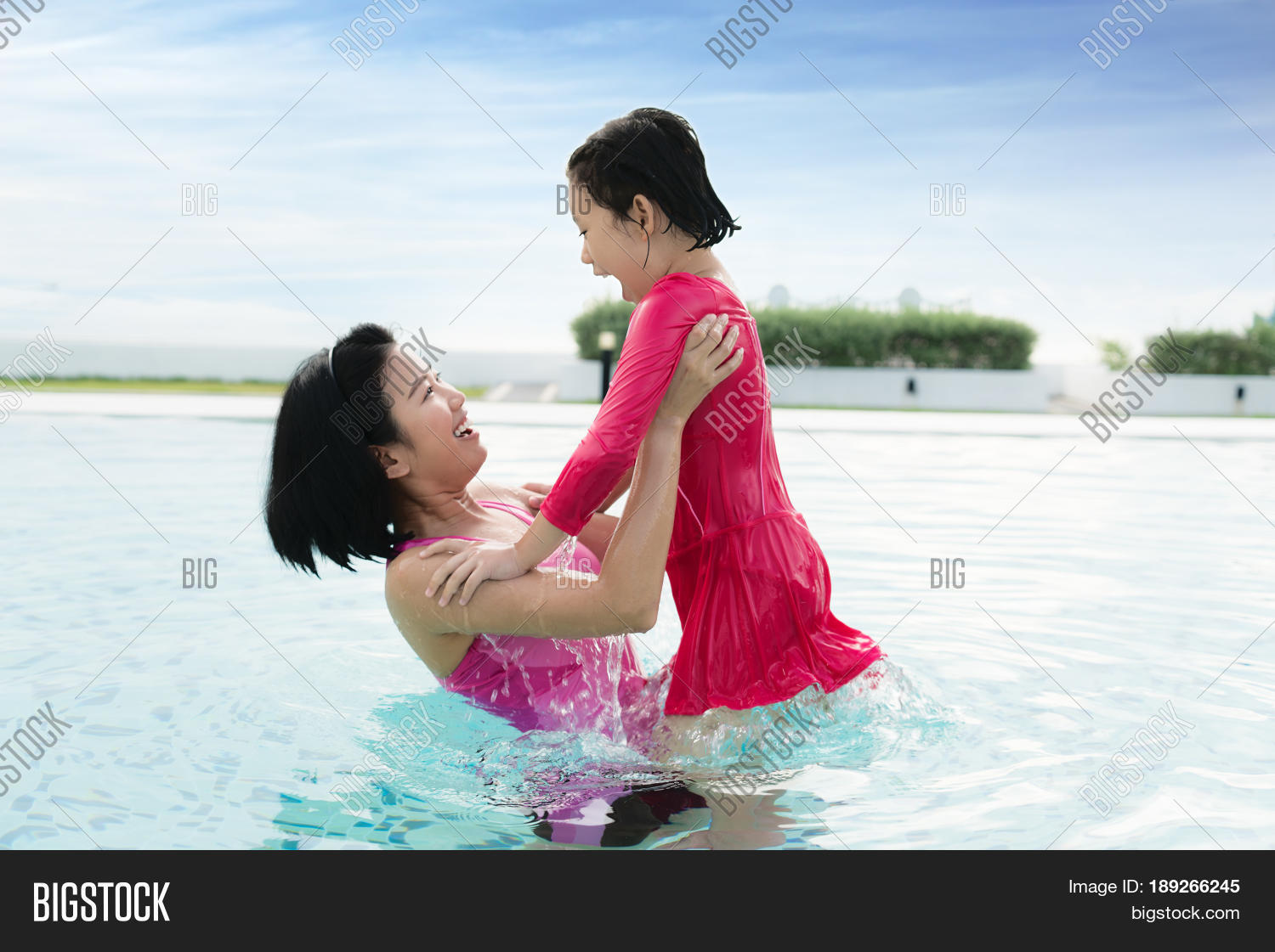 8eb913260f190 Happy Asian mother raise daughter in hotel swimming pool near sea her child  having fun enjoying