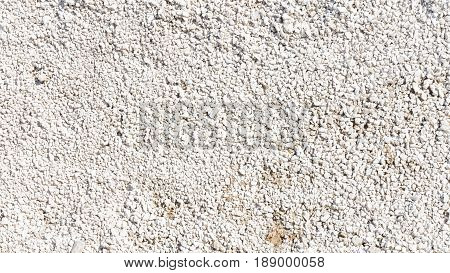 A lot of small white and light gray rubble lies on the road under construction
