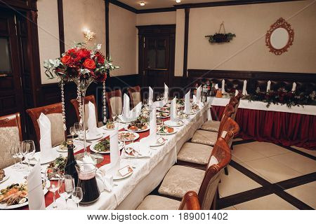 Red Table Centerpiece With Bouquet And Food For Wedding Couple At Wedding Luxury Reception In Restau