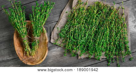 Fresh thyme greens on burlap. Bundles of thyme bandaged with rope in wooden bowl. Gray wooden rustic background. Top view.