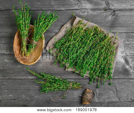 Fresh thyme greens on burlap. Bundles of thyme bandaged with rope in wooden bowl. A small bunch of thyme on gray wooden rustic background. Top view.