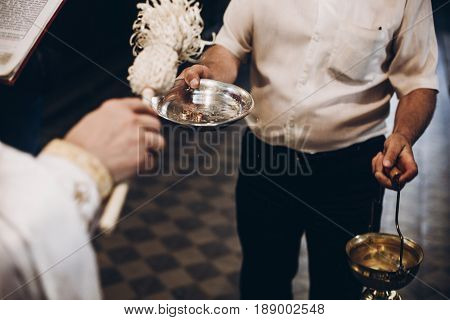 Priest Blessing Golden Wedding Rings On Plate In Church Before Wedding Ceremony, Religion Traditions
