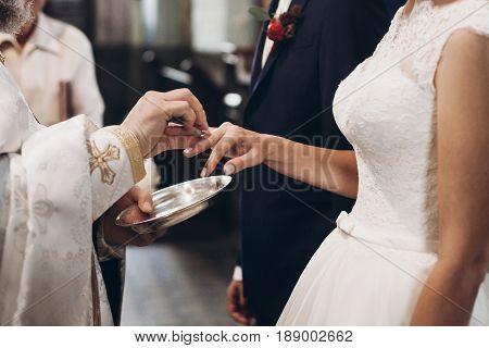 Priest Putting On Golden Wedding Rings On Bride Hand In Church During Wedding Ceremony, Religion Tra