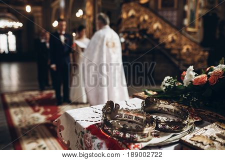 Golden Crowns On Altar And Priest Putting On Golden Wedding Rings On Couple Hand In Church Wedding C