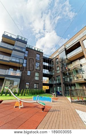 Vilnius, Lithuania - September 30, 3016: Children playground and Modern architecture of apartment residential building. And outdoor facilities.