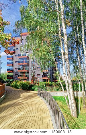 Vilnius, Lithuania - September 30, 3016: Birch trees and Modern glass apartment residential building. And outdoor facilities.