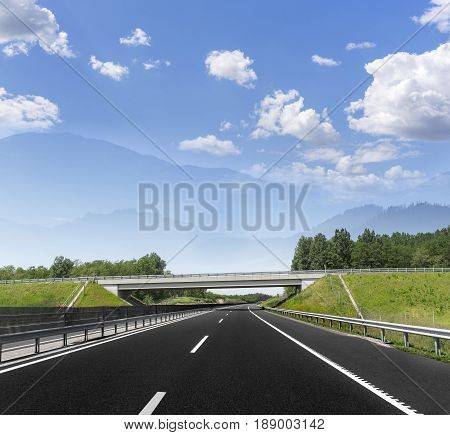 Highway between the forest and the mountains in the distance.