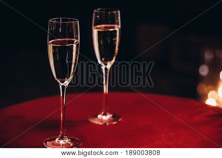 Champagne Glasses On Red Table At Evening Wedding Ceremony Reception, With Lights On Background. Spa