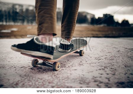 Man male skateboarder on a skateboard is riding in the sunset on the road close-up. Concept street sport in holey boots.