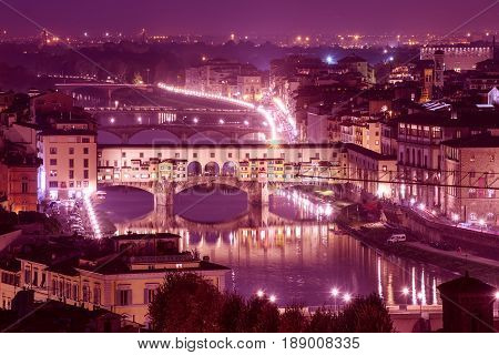 Night view of Florence city with Ponte Vecchio over river Arno and illumination. Travel sightseeing background.