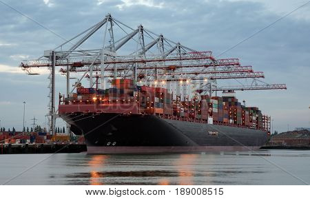Large container ship in port being unloaded