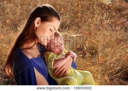 young mother and newborn baby sitting on grass