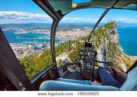 Aerial view of top of Gibraltar Rock. Gibraltar is a territory of South West Europe which is part of the United Kingdom. Helicopter cockpit with pilot arm and control console inside the cabin.