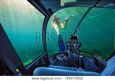 Underwater submarine ship following a young female snorkeling in tropical sea. Woman apnea swims in coral reef with sunbeams. cockpit interior view. Undersea background. Travel concept. poster