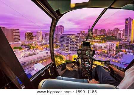 Pink light at twilight of Waikiki cityscape in Oahu island, Hawaii, United States. City night lights and nightlife concept. Helicopter cockpit with pilot arm and control console inside the cabin.