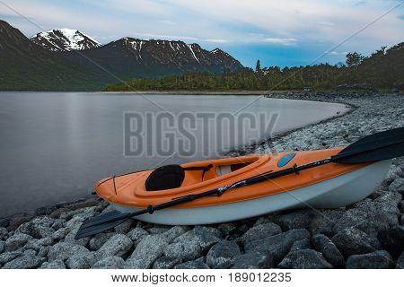 Kayak ready to go beached on rocky shore of Windy Arm of Tagish Lake Yukon Territory Canada