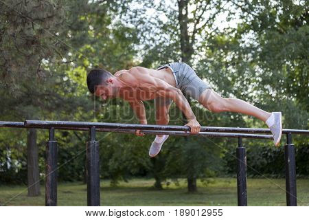 Young Muscular Young Man Doing Exercises On The Parallel Bars