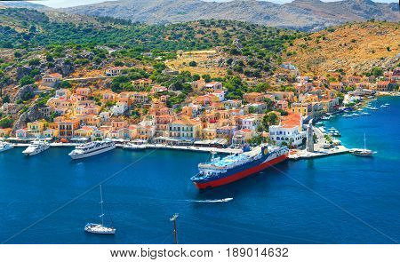 View on beautiful traditional Greek houses on Symi island green hills, yacht sea port, tourist ferryboat at Aegean Sea blue bay. Mediterranean MSC cruises. Greece islands holiday vacation tours trip