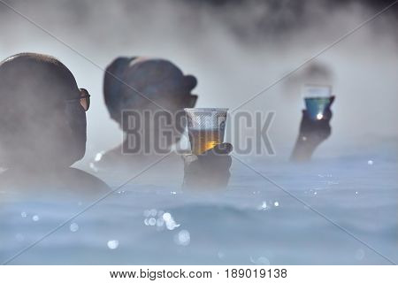 GRINDAVIK, ICELAND - MAY 04, 2015: People in popular Blue Lagoon thermal bath in Iceland. You can buy drinks at the bar while soaking in the steaming water.