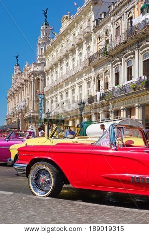 HAVANA,CUBA - MAY 29, 2017 : Vintage american cars parked waiting for tourists next to a hotel in Old Havana