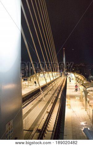 Gece köprüde tren istasyonunda tren bekleyen insanlar