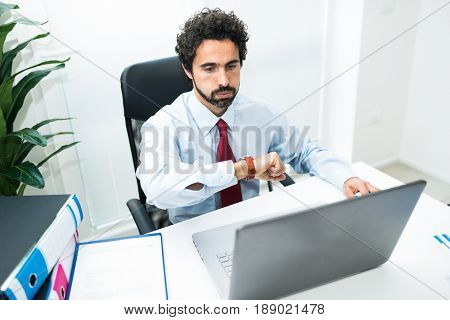 Tired and bored businessman looking at his watch