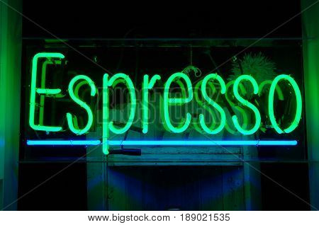 Green and blue espresso neon sign hanging in a window