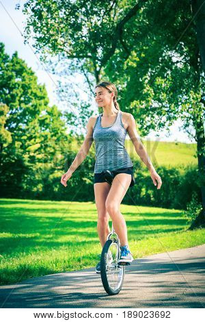 young athletic woman unicycling outdoors, having fun