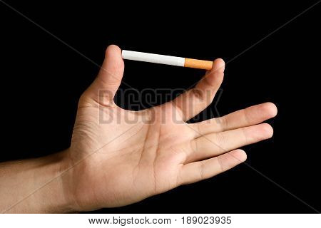 Man's Hand Holding A Cigarette Between Index Finger And Thumb. Isolated On Black Background