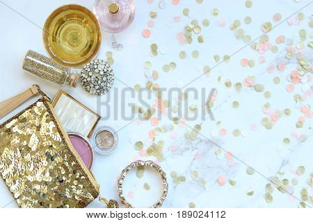 Gold sequined bag with fashion and beauty supplies spilling out. Pink confetti. Champagne glass. White marble copy space.