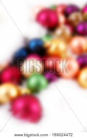 Pile of Christmas ornaments nestled in white feathers - blurred image background