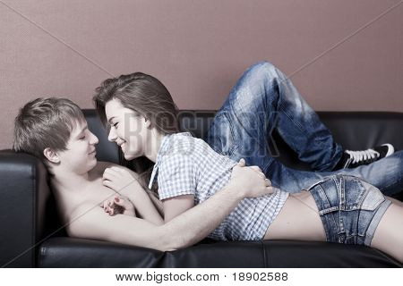 beautiful caucasian couple lying down on sofa