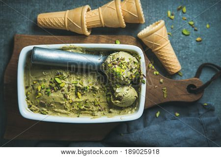 Homemade pistachio ice cream in ceramic mold with metal scooper, crashed pistachio nuts and waffle cones over dark concrete background, top view, selective focus