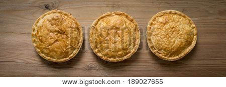 Overhead View Of Three Cooked Round Meat Pies On Wooden Countertop