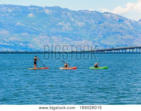 Group of kayakers and a paddleboarder enjoying summer beach activities
