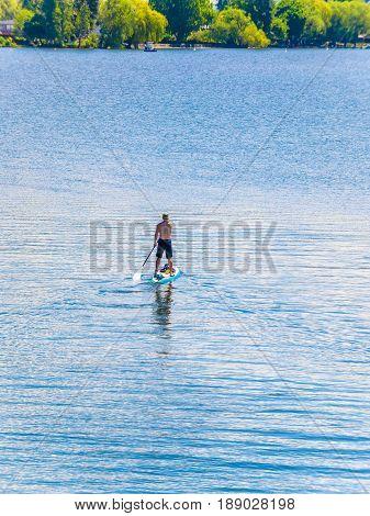 Man on a paddleboard paddling toward the lake beach