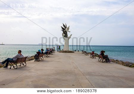 Unidentified Turkish people relax around the Hand Of Peace Monument in Kusadasi, Aegean Coast, Turkey