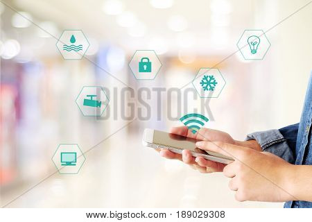 Hand using smart phone as smart home control application over blurred bokeh background smart home concept