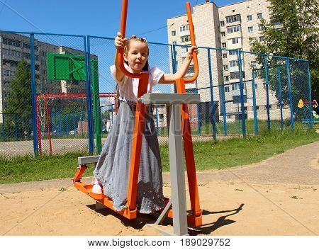 The girl does exercise on the playground
