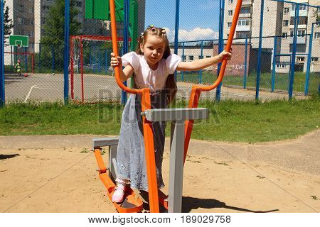 The girl of seven years does exercise on the playground