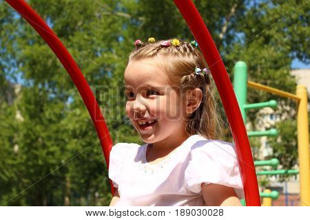 Seven-year-old girl swinging on a swing at the playground